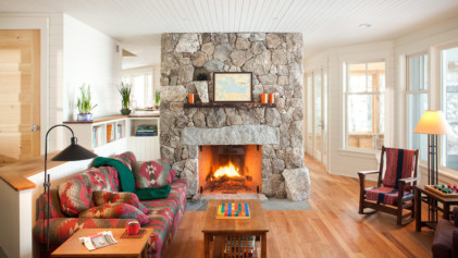 Wood-burning fireplace with stone chimney in cottage-style home.