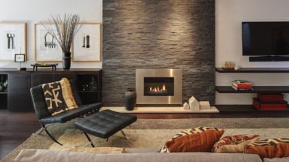 Gas fireplace within black stone wall.